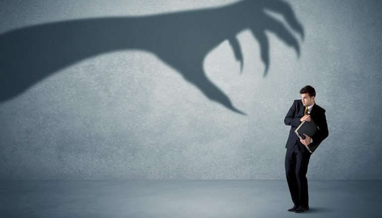 Man holding his data afraid of a big monster claw shadow showing the fear of online threats