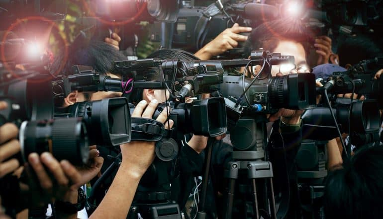 Press and media camera video photographer at press conference showing the need to protect corporate reputation with effective data breach response