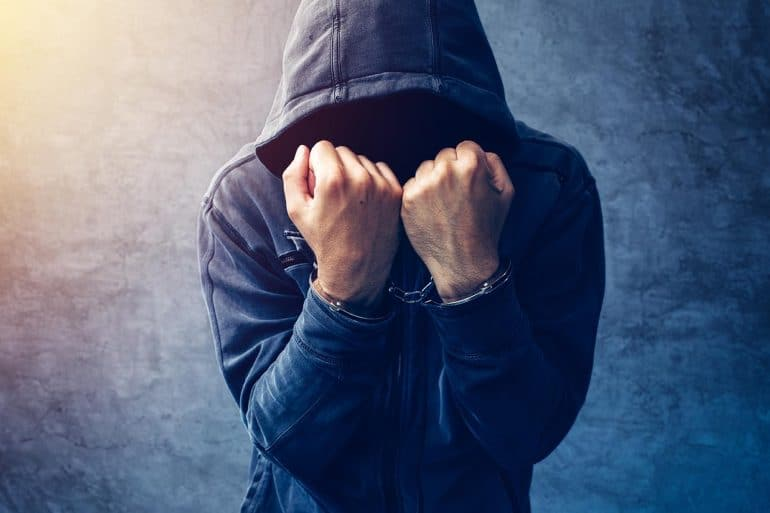 Arrested hacker with handcuffs wearing hooded jacket shows how Russian hackers pose a persistent threat to the world