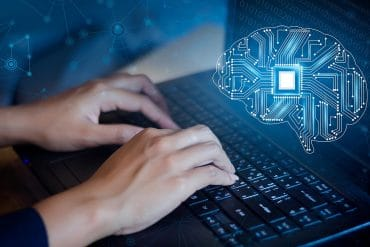Man typing on a keyboard programming artificial intelligence posing the threat of AI to cybersecurity