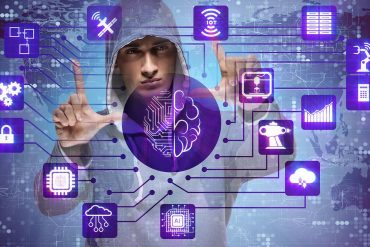 Man in hoodie manipulating artificial intelligence screen showing impact on cybersecurity