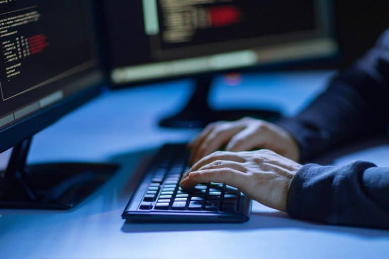 Hands of hacker in dark room writing code for cyber attack showing problem of cybersecurity skills shortage