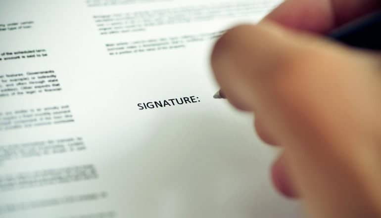 Closeup of a young man about to sign a document with a pen under the word signature showing marketing consent
