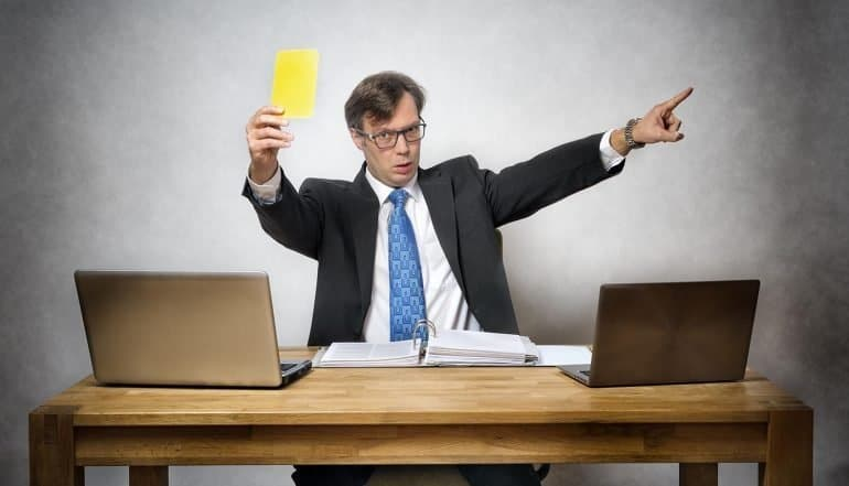 Regulator holding up yellow card in office showing the millions in ICO fines levied for 2018