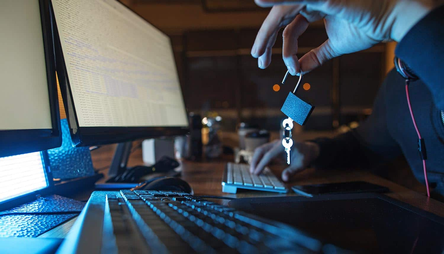Close up hand of cybercriminal downloading data from Marriot data breach while holding an opened lock and key