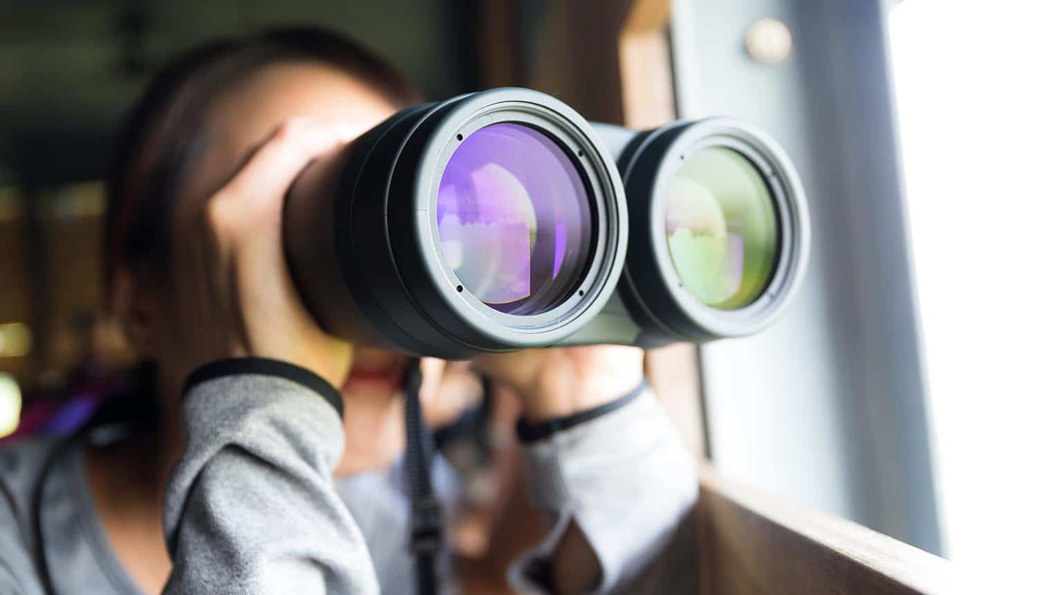 Young woman using binoculars to look into the future showing the need to look beyond regulations for the privacy industry