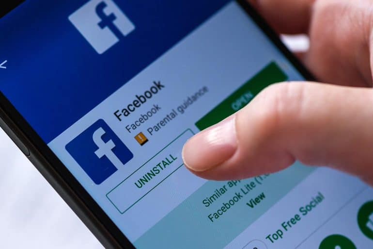 Finger hovering over uninstall button for Facebook app showing a woeful year for Facebook