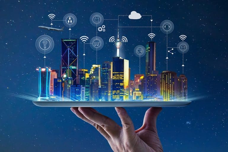 Hand holding an empty digital tablet with Smart city with smart services and icons of internet of things showing smart cities embracing digital rights