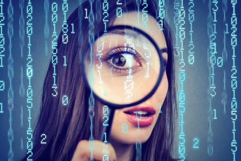 Curious woman looking through a magnifying glass against computer binary code background showing the extent of surveillance capitalism