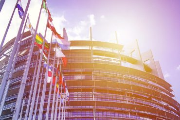 EU Parliament building with flags in sun light showing a new era for privacy regulations and GDPR