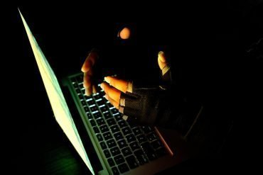 Human hand on the keyboard of notebook in the darkness. showing cyber fraud by Chinese hackers