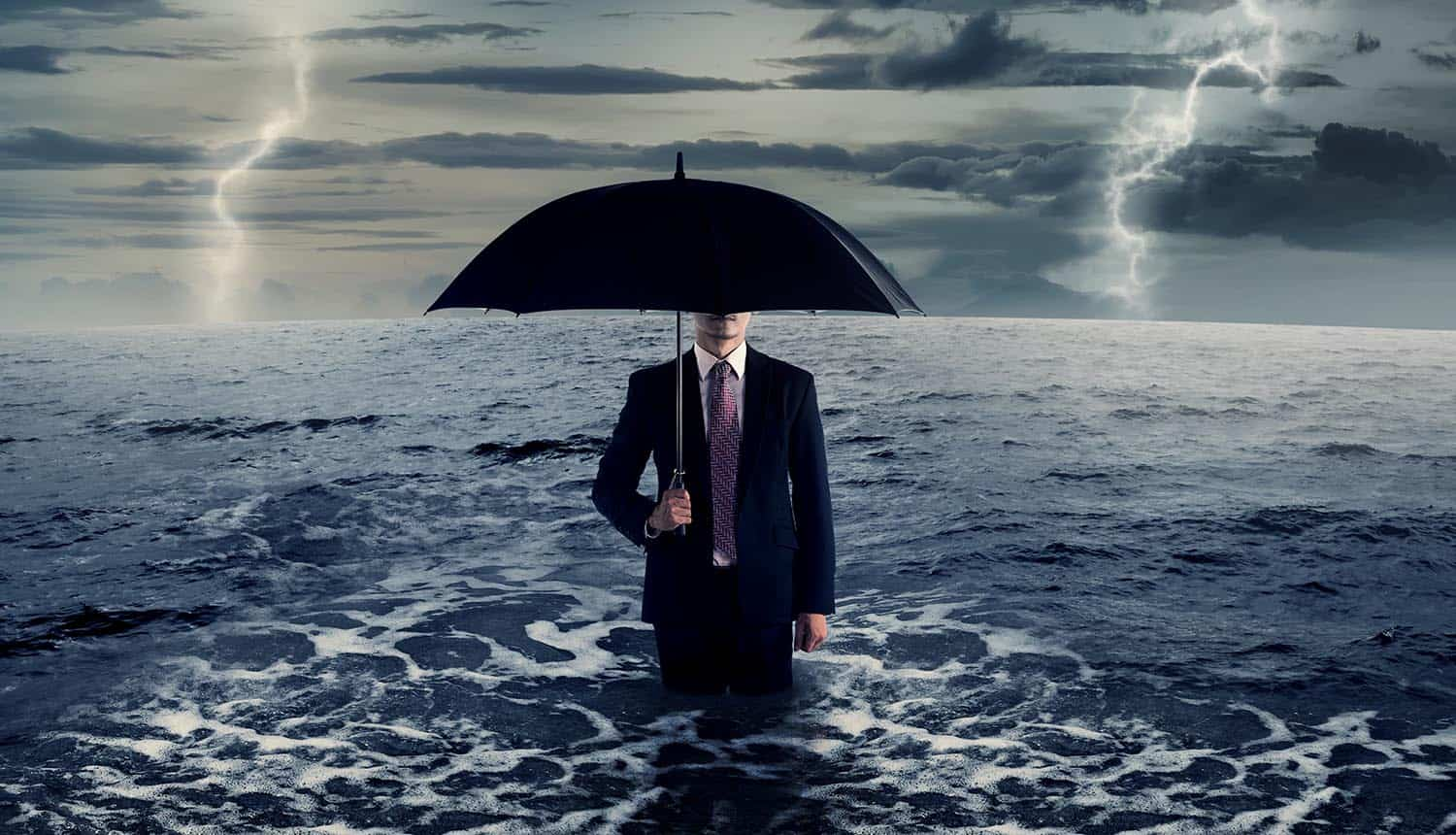 Business man standing on the sea in the middle of storm showing cyber insurance may not cover cyber war