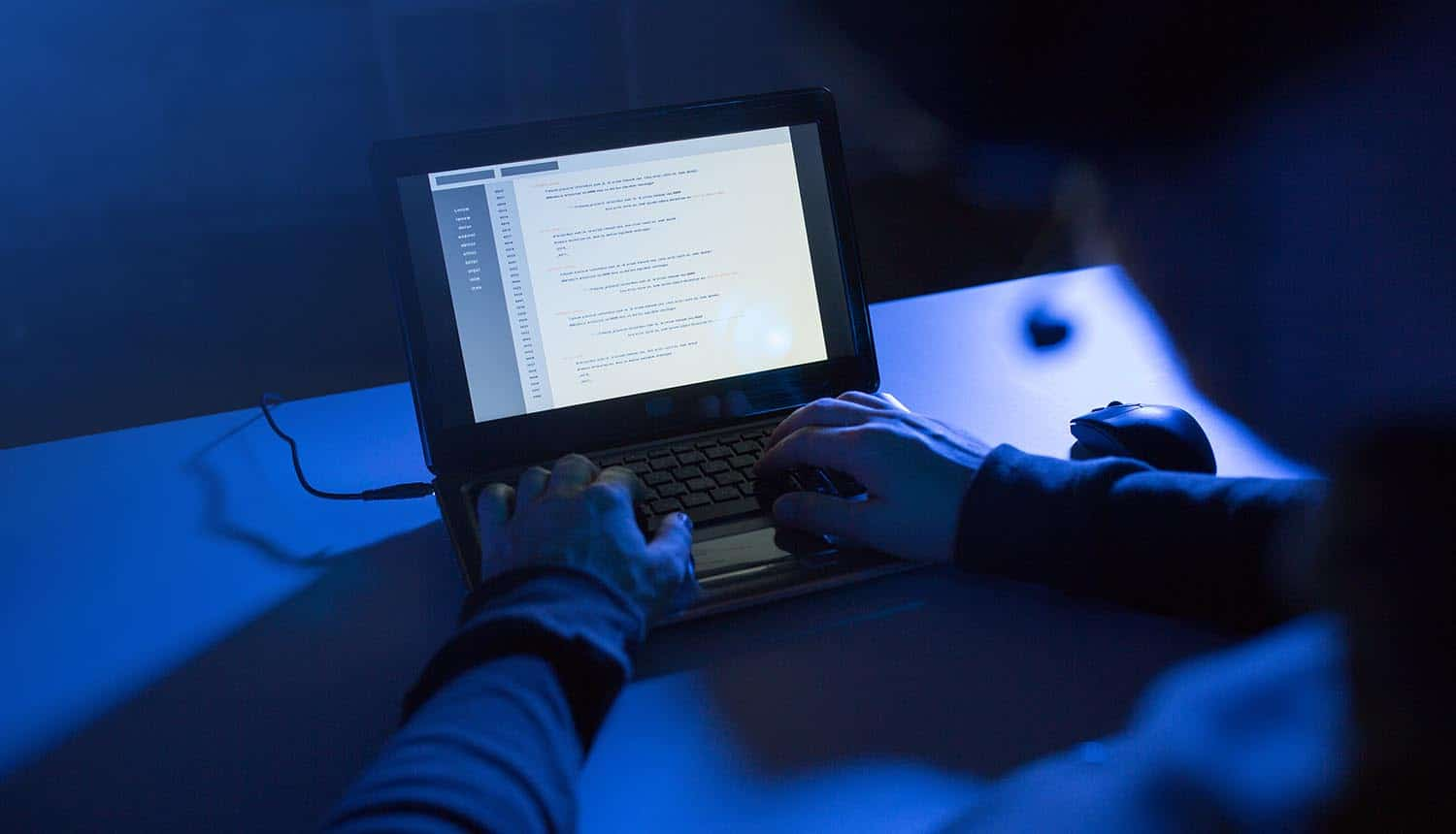 Hands of hacker in dark room showing need for identity theft protection services