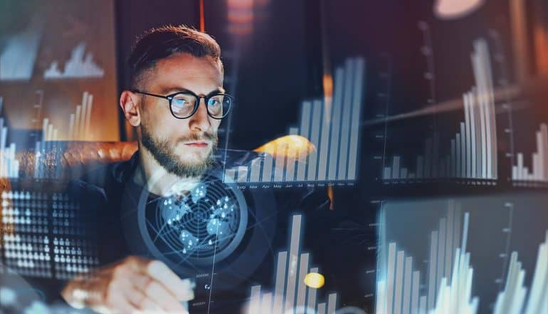 Man looking at screen with data analytics and insider threat intelligence