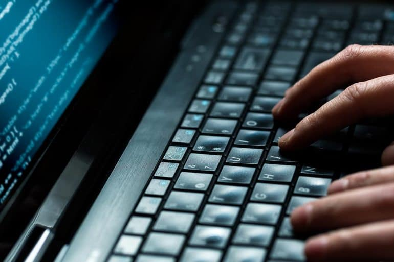 Hacker using laptop to execute a cyber heist