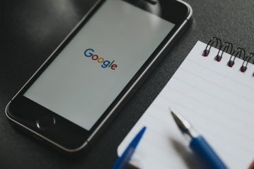 Google app in iPhone screen, placed on a black work space showing Apple's consumer privacy business strategy