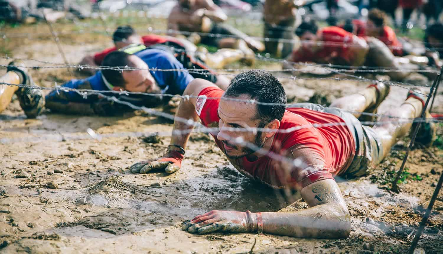 Participants in extreme obstacle race crawling under barb wires showing the difficulty of navigating the privacy minefield