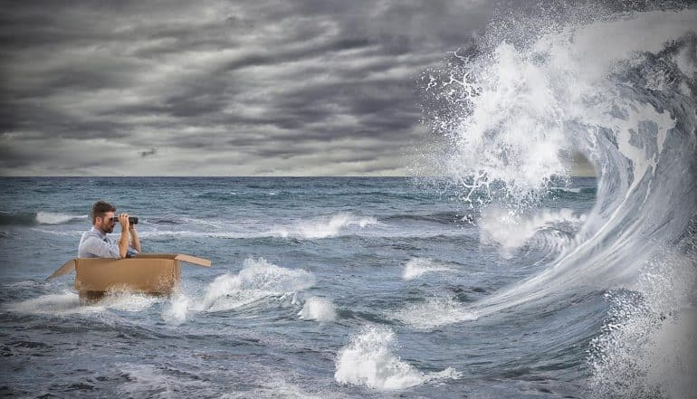 Businessman in a cardboard sails in a storm at sea, looking ahead using binoculars at the threat landscape
