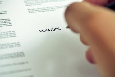 Closeup of man about to sign a privacy consent document with a pen under the word signature