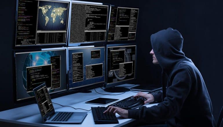 Rear View Of A Hacker Using Multiple Computers Showing Top Information Security Risks