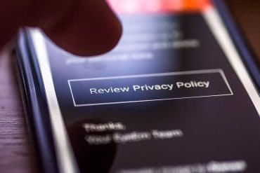 Closeup of human finger pointing to smartphone message with button Review Privacy Policy showing the problem with GDPR and transparency