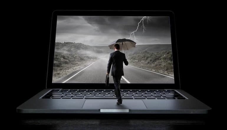 Man holding umbrella walking into a laptop with lightning on the screen showing how insurers have a role in tackling cyber threats