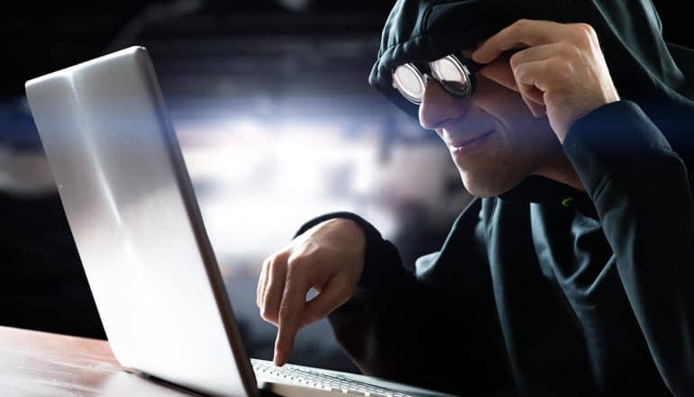 Hacker in front of his computer performing a formjacking attack