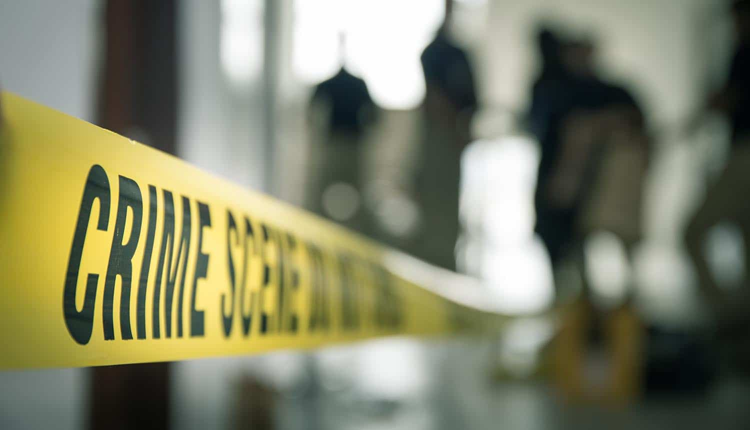 Crime scene tape with blurred forensic law enforcement background showing need for digital forensics