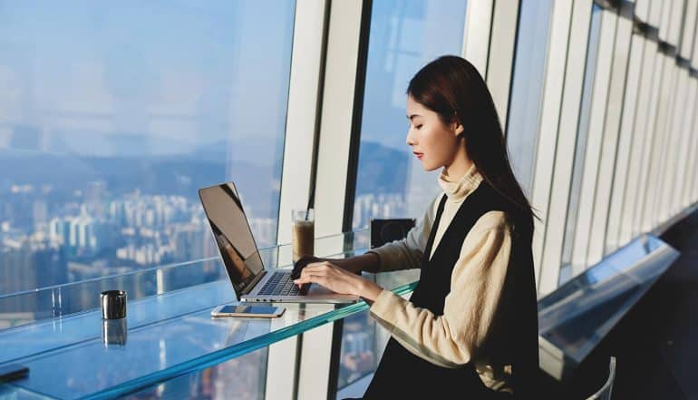 Woman working on her laptop near hotel window showing managing risk in the digital era