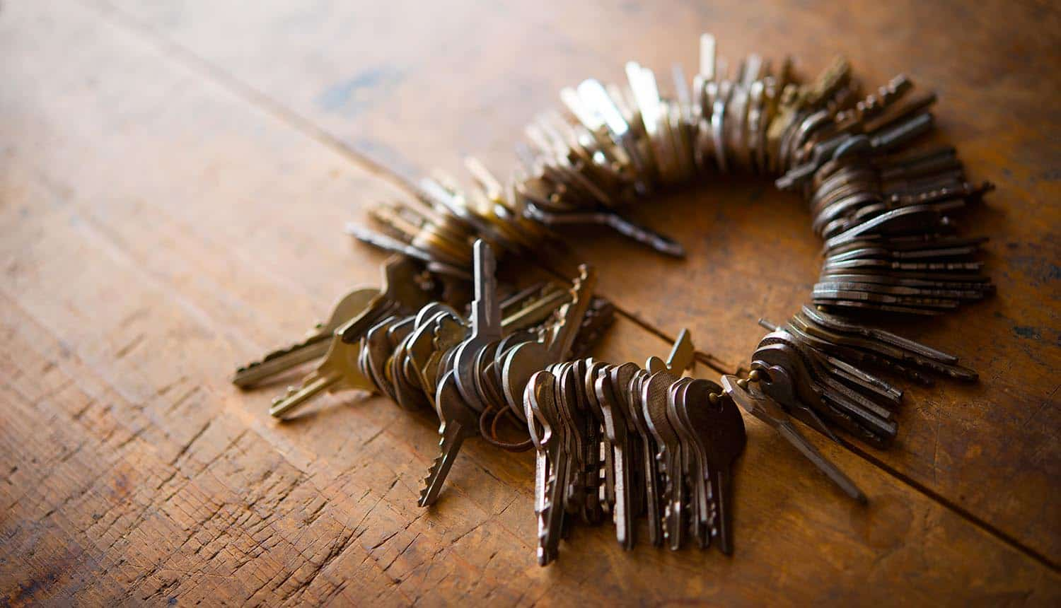 Many old keys on a well used old wooden desk show security flaws in password managers