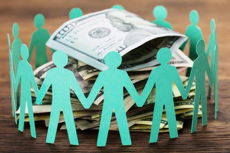 Paper cut out human figures around stack of hundred dollar bills showing concept of digital dividends and data monetization revenue sharing
