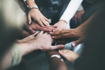 Joining hands together as a team showing the need to focus on both information security and data privacy