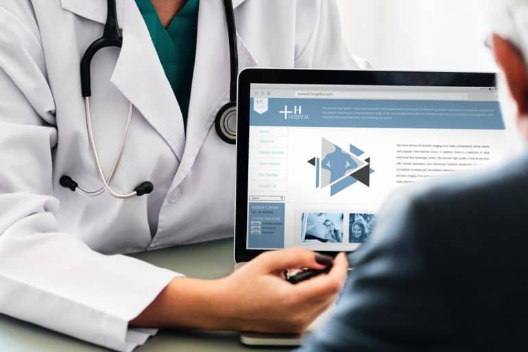 Doctor explaining medical information to patient showing the need for HIPAA compliant patient communication