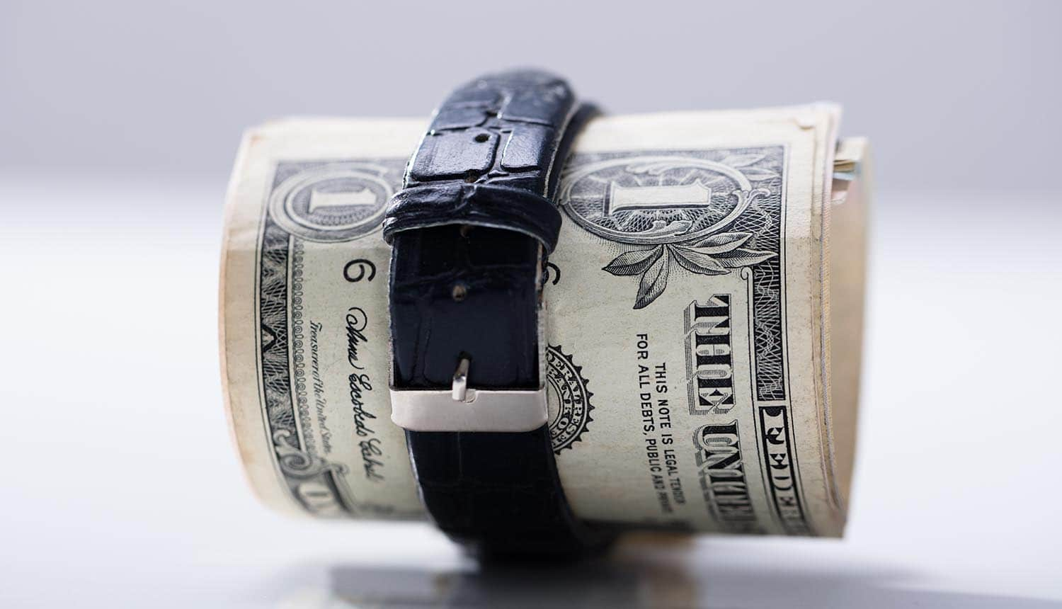Rolled up dollar banknotes tied with belt showing the cost of privacy regulations on small businesses
