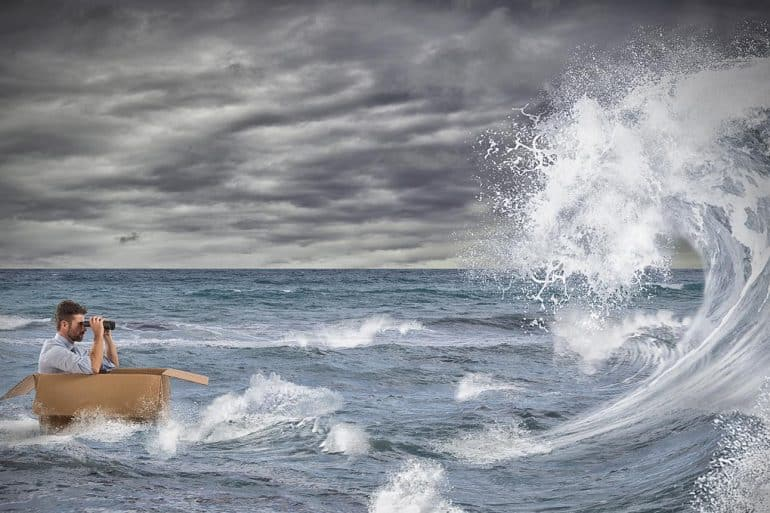 Businessman in a cardboard sails in a storm at sea showing how organizations cope with GDPR and CCPA regulations
