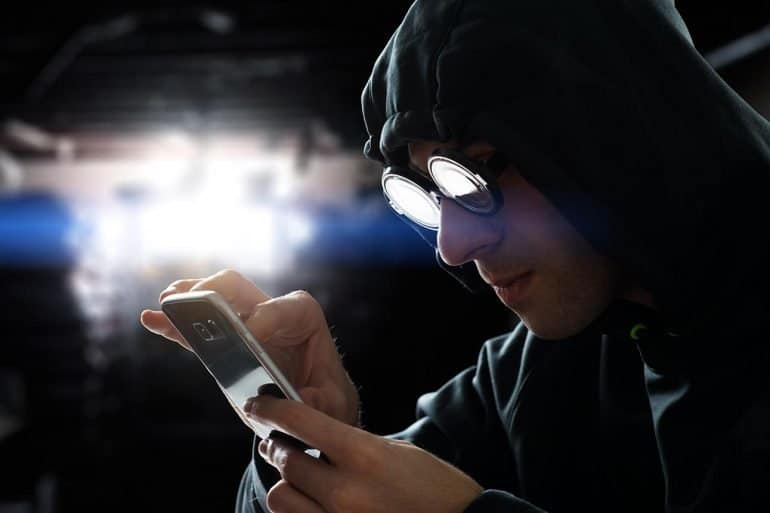 Hacker touching a smart phone screen showing how hackers attack mobile apps and the methods to protect against it