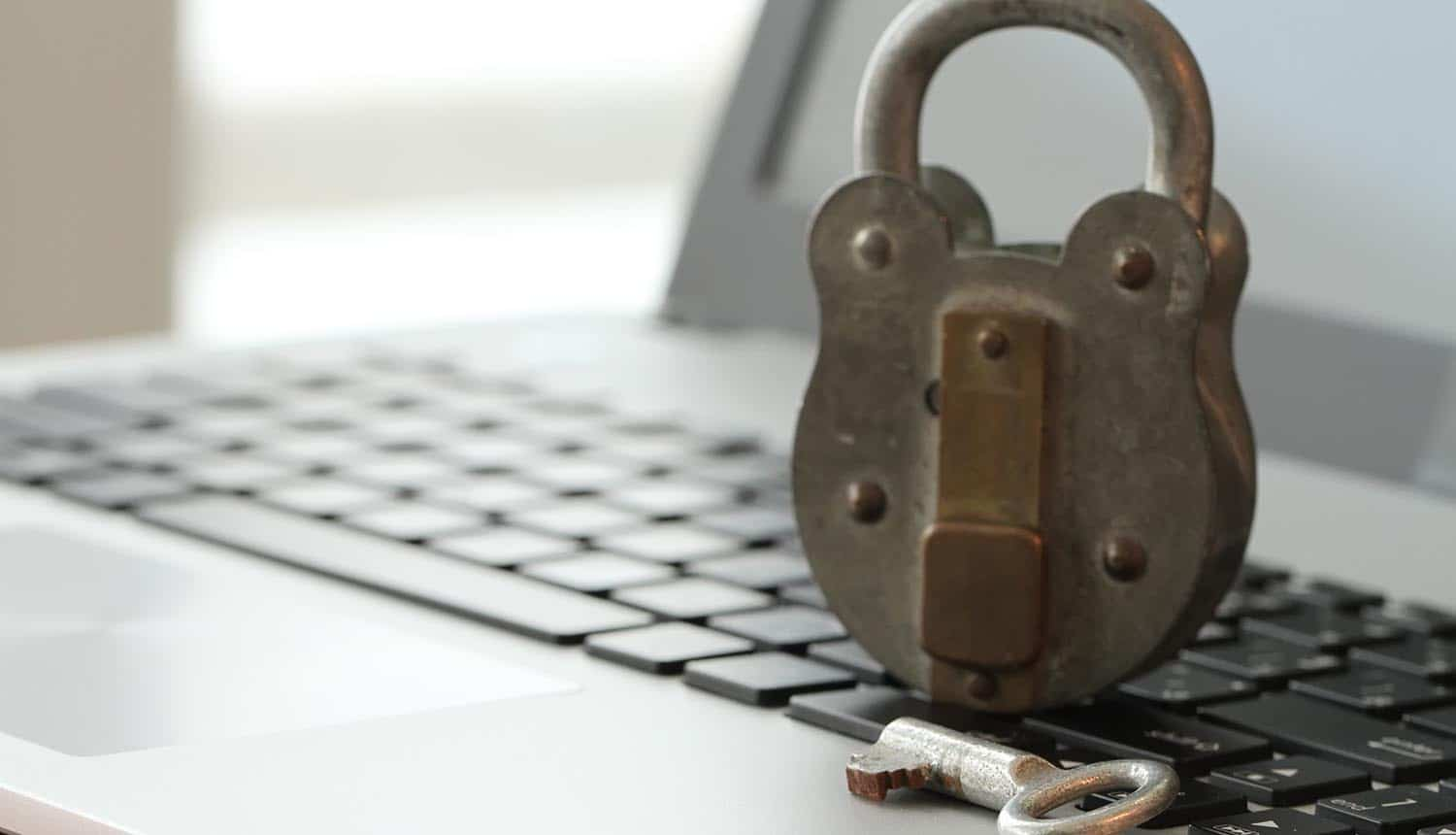 Old padlock and key on laptop computer keyboard showing the need for small businesses to stay safe online