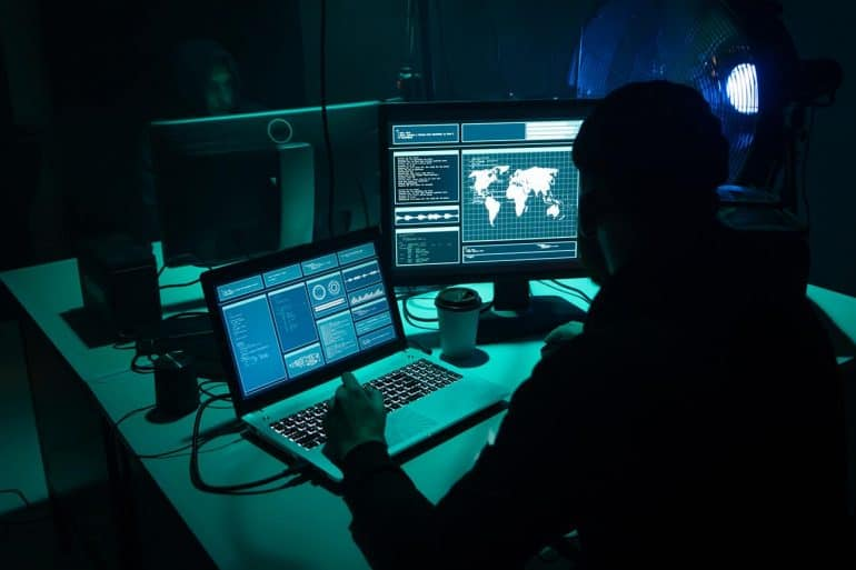 Hacker working in front of laptop showing extension of attacks to political, diplomatic and military targets in U.S, Australia, and U.K by Iranian hackers