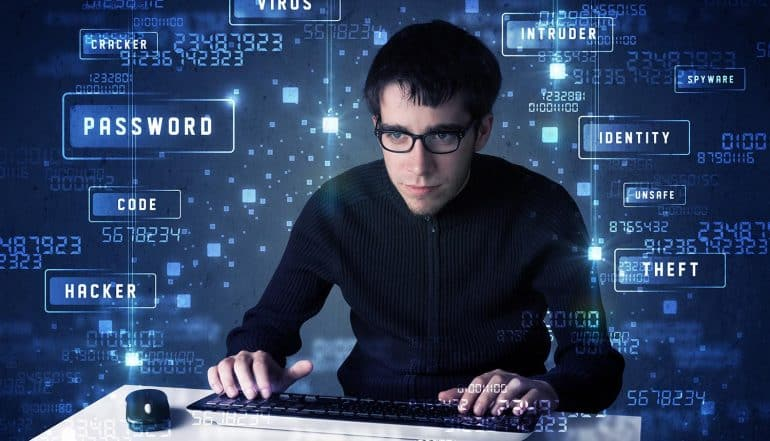 Hacker programming in technology environment showing profitability of cyber extortion