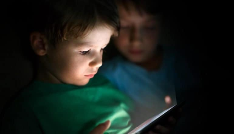 Boy playing tablet showing possible new DETOUR Act to stop tech companies in using dark patterns to obtain consent or user data