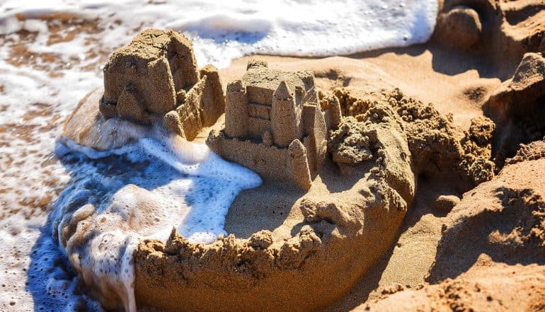 Waves wash away sand castles on the beach showing how businesses have trouble achieving cyber resilience