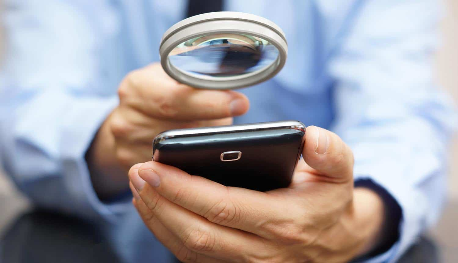 Businessman using mobile smart phone with magnifying glass showing many ways which mobile opens the door for fraud