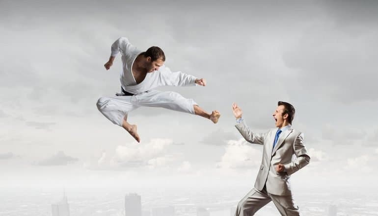 Karate man fighting businessman showing the aggressive changes to deterrence, international response and use of offensive cyber capabilities on the horizon