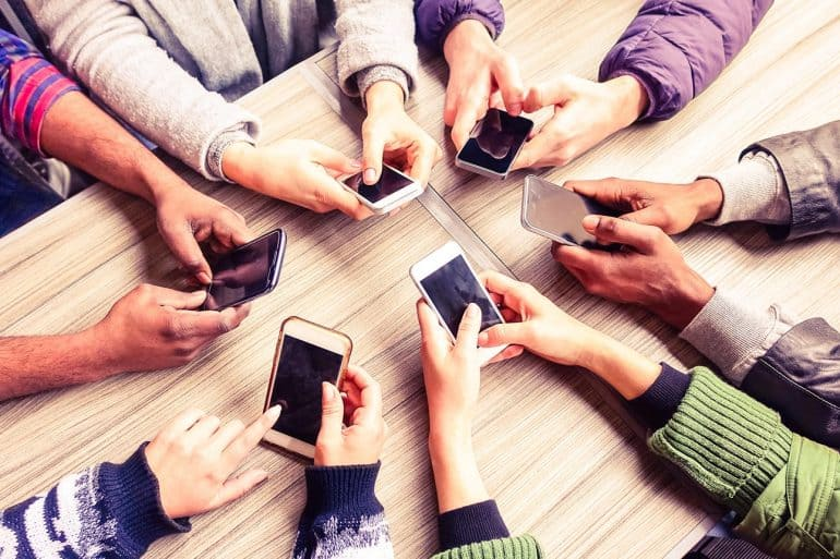 Hands of multiple people on mobile phones showing the progression to edge computing to provide latency and privacy benefits to users