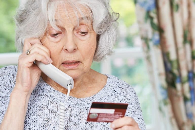 Senior woman giving credit card details on phone showing $2.7 billion in personal and business losses through internet crime