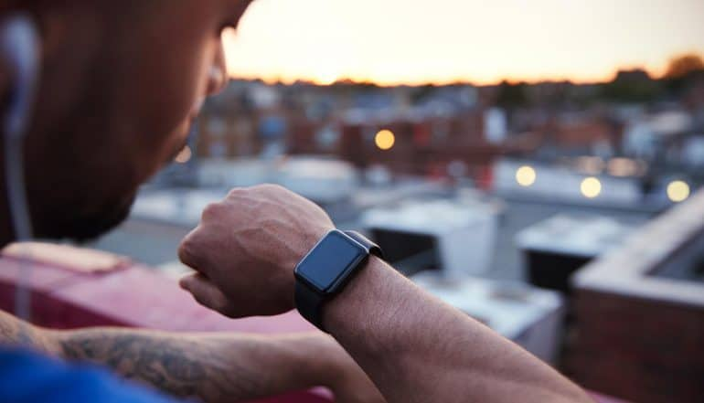 Runner checking fitness tracker showing potential use of fitness tracker technology to defend against cyber attacks