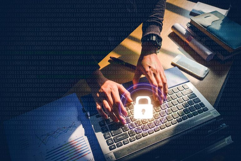 Padlock against hands on keyboard showing tips for businesses to prevent data breach