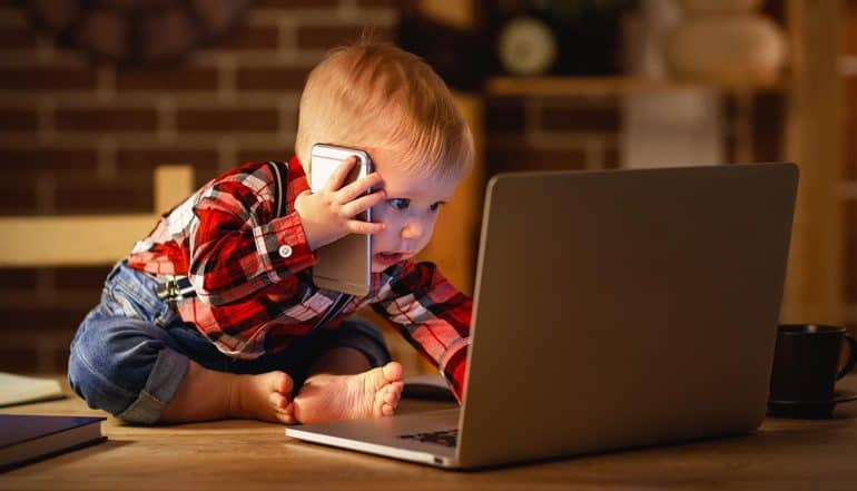 Child working on computer and talking on phone showing U.S. and U.K. turning their attention to children's privacy online