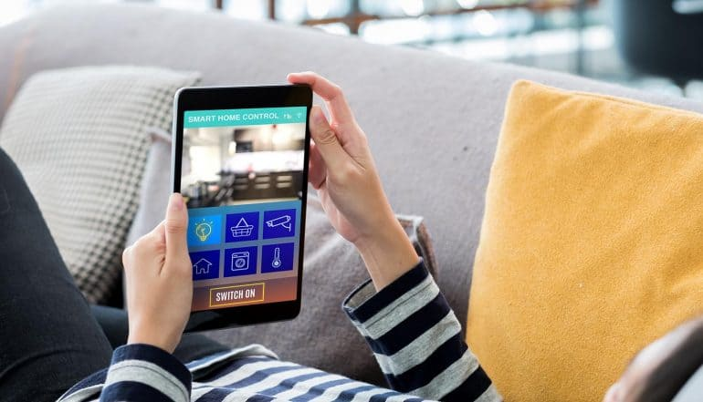 Hand on tablet using smart home system showing new IoT security laws in U.K. and U.S. to protect consumers from hacks of internet-connected devices