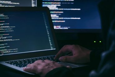 Hacker working on software code showing source code breach at major anti-malware vendors by Russian hackers